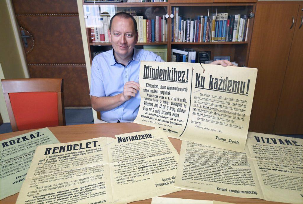 Richard Pavlovič, a Kassai Állami Levéltár igazgatója a Szlovák Tanácsköztársaság idején kiadott magyar és szlovák nyelven kiadott rendeleteket mutatja a Kassai Állami Levéltár kutatótermében. Fotó: TASR