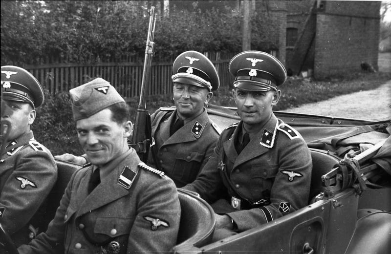 1939 szeptember, Lengyelrszág, Ustronice / Opatowice közelében; a lengyel és a náci Németország biztonsági rendőrsége felügyelete alatt álló letartóztatott zsidók úti ellenőrzése. Négy rendőr ül egy kabrioletben: balról jobbra, egy Oberscharführer, egy Rottenführer egy Untersturmführer és egy Oberscharführer. Forrás: Deutsches Bundesarchiv.